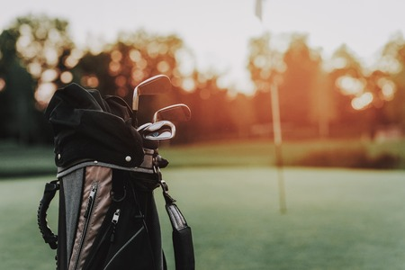 Golf Sticks in Black Bag on Green Field with Flag. Green Grass. Sport in Summer Concept. Outdoor Fun Concept. Flag on Stick. Sunny Day. Sport on Field Concept. Steel Golf Stick. Black Bag. Stockfoto - 108292461