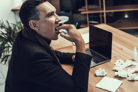 Sick Man in Suit with Scarf Sitting in Office. Manager in Modern Office. Healthcare Concept. Modern Office. Sick Worker. Healthcare in Office. Wooden Table. Digital Device. Laptop on Desk.