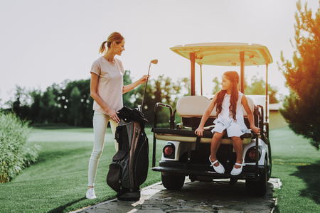 Young Mother and Daughter with Cart on Field. Happy Family. Little Girl. Driver with Car. Healthy Lifestyle Concept. Golf Club. Sports in Summer. Vehicle on Field. Outdoor Fun in Summer. Foto de archivo - 108048522