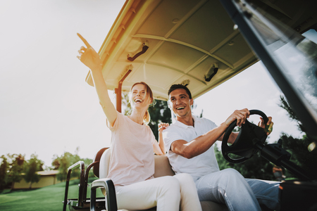 Happy Young Couple in White Cart on Golf Field. Young Family. Golf Club. Sports in Summer. Vehicle on Field. Outdoor Fun in Summer. Driver with Car. Healthy Lifestyle Concept. Couple on Vacation. 写真素材