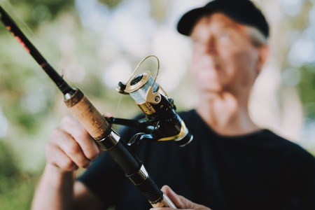 Old Man with Gray Hair Fishing on River in Summer. Relaxing Outdoor. Sitting Grandfather. Man near Lake. Fishing Rod in Hands. Sports in Summer. Old Man in Cap. Weekend on River. Aged Fisherman.