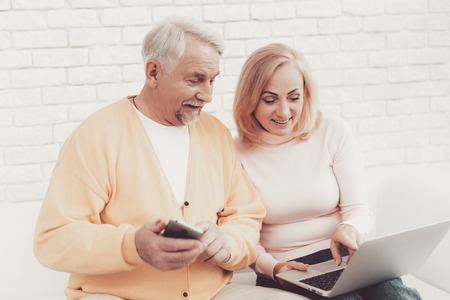 Old Man near Old Woman with Smartphone and Laptop. Sitting on White Sofa. Woman with Laptop. Grandfather and Grandmother. Family at Home. Using Digital Gadget. Holding Cell Phone in Hands. 스톡 콘텐츠