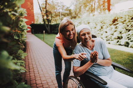 Patient Undergoes Rehabilitation. Cancer Patient on a Wheelchair. Woman with Daughter. Woman Glad See Daughter. Recovering Woman. Remission. Clinic. Cancer Patient. Medical History. Smiling Women. Walks. Having Fun.