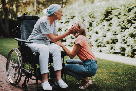 Patient Undergoes Rehabilitation. Cancer Patient on a Wheelchair. Woman with Daughter. Woman Glad See Daughter. Recovering Woman. Remission. Clinic. Cancer Patient. Medical History. Smiling Women. Walks. Having Fun. Daughters Cheeks.