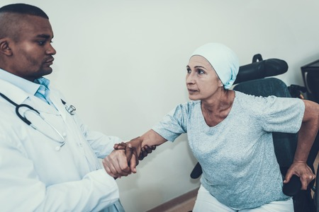 Doctor in Clinic. Doctor Helps get up. Patient Undergoes Rehabilitation. After Treatment for Cancer. Cancer Patient on a Wheelchair. Doctor with Stethoscope. Stethoscope on Neck. Scarf on Womans Head. Reklamní fotografie