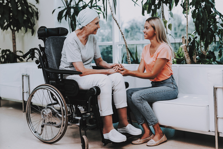 Patient Undergoes Rehabilitation. After Treatment for Cancer. Cancer Patient on a Wheelchair. A Woman with Daughter. Woman Glad See Daughter. Recovering Woman. Remission. Clinic. Cancer Patient.