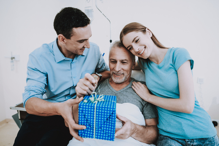 Gift for Old Man in Clinic. Young Family give Old Man Gift. Happy Family. Good Mood in Family. Family in Clinic. Old Man and Family in Hospital. Health Man and Family in Clinic. Care about Old Man.