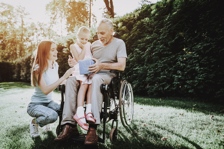 Happy Family on Nature with Child. Family and Caregiver. Child and Old Man. Health Girl with Aged. Happy Family Life with Old Man in Wheelchair. Wheelchair and Old Man with Family. Man in Stroller. Stock Photo