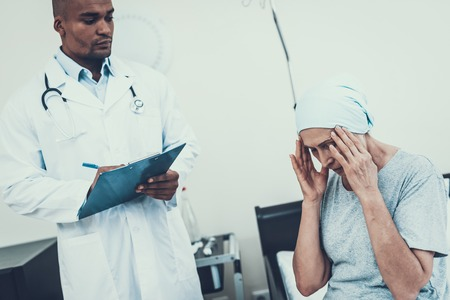 Doctor Interviews. Woman Undergoes Rehabilitation. After Treatment for Cancer. Woman on Bunk. Headache. Doctor Fills Form. Form in Hands. Scarf on Womans Head. Woman Sitting on Bunk.