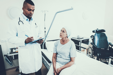 Doctor Interviews. Woman Undergoes Rehabilitation. After Treatment for Cancer. Tablet for Papers. Doctor with Papers. Sitting woman. Patient Talks. Women Tell about her Condition . Фото со стока