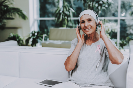 Patient Undergoes Rehabilitation. Cancer Patient on Sofa. Recovering Woman. Remission. Clinic. Cancer Patient. Flowerpots with Flowers. Pink Ribbon. Breast Cancer. Music on Tablet. White Headphones. Фото со стока