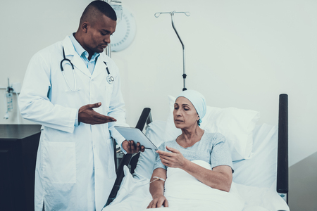 Doctor stand in Ward. Cancer Patient. Tablet with Medical History. Doctor Interviews. Woman Undergoes Rehabilitation. After Treatment for Cancer. Tablet for Papers. Woman on Bunk .