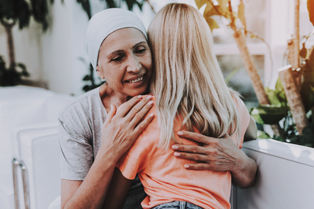 Patient Undergoes Rehabilitation. Cancer Patient on Sofa. Woman with Daughter. Recovering Woman. Remission. Clinic. Cancer Patient. Smiling Women. Hugging Women. Lobby. Flowerpots with Flowers.