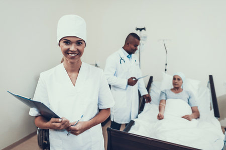 Nurse Posing. Background Patient. Nurses Notes. Woman Undergoes Rehabilitation. After Treatment for Cancer. Doctor Puts a Dropper. Doctor in Clinic. Cancer Patient. Doctor Gives a Pill. Фото со стока