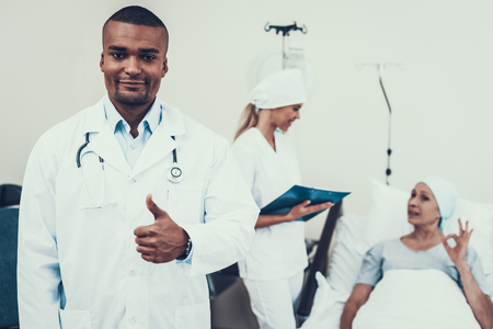 Doctor Posing. Background Patient. Doctor Shows Thumbs-Up. Woman Undergoes Rehabilitation. After Treatment for Cancer. Woman on Bunk. Nurse Holds a Blank. Doctor in Clinic. Cancer Patient.