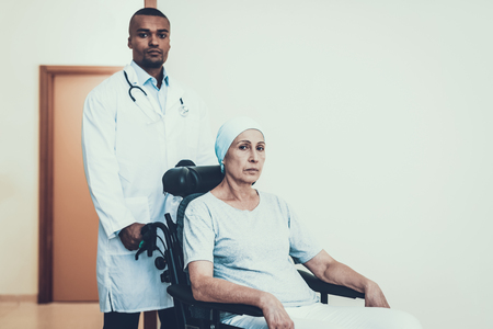 Doctor in Clinic. Woman Rides to the Ward. Patient Undergoes Rehabilitation. After Treatment for Cancer. Cancer Patient on a Wheelchair. Doctor with Stethoscope. Stethoscope on Neck. Doctor Stand.