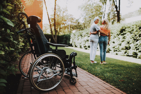 Patient Undergoes Rehabilitation. Cancer Patient Stands Up . Woman with Daughter. Woman Glad See Daughter. Recovering Woman. Remission. Clinic. Cancer Patient. Embrace. Woman Nearby Wheelchair.