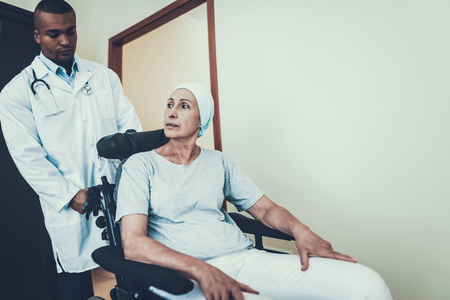 Doctor in Clinic. Woman Rides to the Ward. Patient Undergoes Rehabilitation. After Treatment for Cancer. Cancer Patient on a Wheelchair. Doctor with Stethoscope. Stethoscope on Neck. Фото со стока