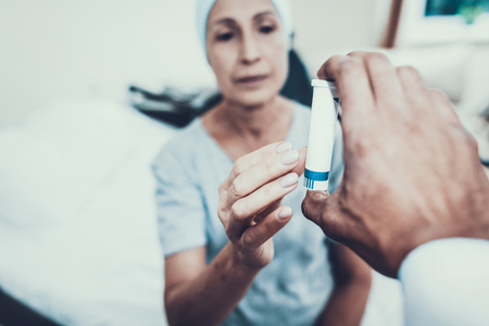 Doctor Gives a Pill. Patient Undergoes Rehabilitation. After Treatment for Cancer. Patient on a Cot. Woman Takes Pills. Doctor with Stethoscope. Stethoscope on Neck. Scarf on Womans Head.