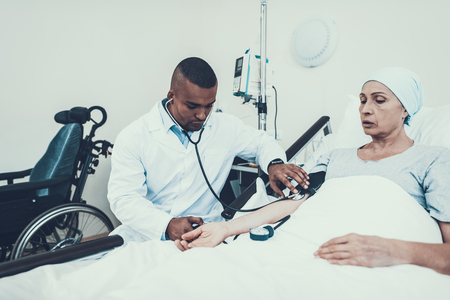 Doctor Measures Pressure. Patient Undergoes Rehabilitation. After Treatment for Cancer. Woman on Bunk. Tonometer. Stethoscope. Doctor in Clinic. Cancer Patient. Scarf on Womans Head