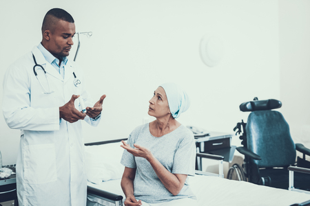 Doctor Tell about Pill. Patient Listen Attentive. Patient Undergoes Rehabilitation. After Treatment for Cancer. Patient on a Cot. Doctor with Stethoscope. Stethoscope on Neck. Scarf on Womans Head. Фото со стока
