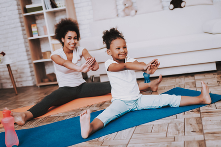 Mother and Little Girl Training Together. Studio and Sportwear. Mulatto Training Together. Mother Help Little Girl. Relaxation with Moter in Good Day. Sportwear with Mother. Mother Learn Young Girl.