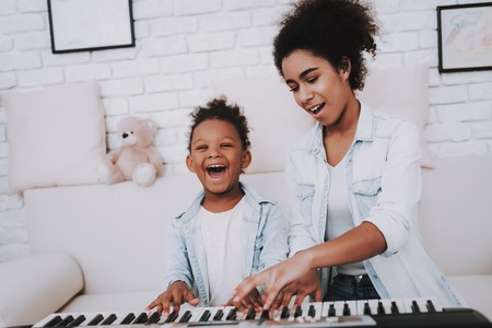 Babysitter Learn Piano with Young Girl. Education with Young Girl. People Play in the Piano. Hobbies Mother and Daughter. Happiness and Smile. Little Girl with Mother. Laugh Together. Smile Girl. 写真素材 - 108850221
