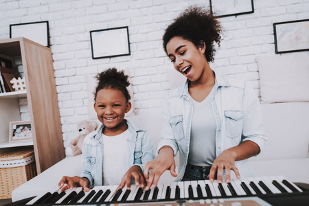 Mulatto and Young Girl Play Together. Smile and Happy Girl. Positive Time. Happiness Girl. Hobbies with Mother. beautiful Girl Play on Piano. Positive Emotion and Good Smile. Daughter and Mother. 写真素材