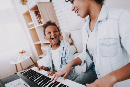 Cute and Little Girl Lough and Smile with Mother Happy Time with Mother. Positive Emotion with Mother. Relax Time with Mom Teacher Mom with Young Girl Play on Piano. Beautiful Mother Help Young Girl. 写真素材