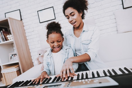 Mother with Daughter Play on Piano. Mother Help Girl with Piano. Positive Emotion. Smile Girl and Smile Mother. Positive Day with Beautiful Mother. Time for Play on Piano. Funny Mother and Happy Girl.