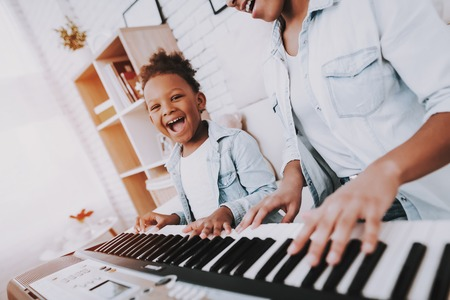Funny Girl amd Happy Mother Play on Piano Together. Hobbies For Mother and Young Daughter. Happy Mother with Little Girl Play on Piano. Positive Day for Beautiful Woman. Mulatto with Young Daughter. Stockfoto