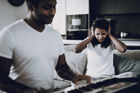 Afro American Girl Hurt From Boyfriend's Synthesizer Playing. Working Musician. Musical Hobby. Hands On Keyboard. Couple Quarrel. Bad Idea. Painful Music Sounds. Stuffed Ears. Family Disharmony. Stock Photo