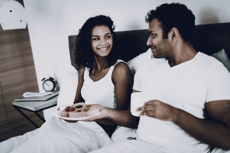 Afro American Couple Having A Dinner In Bedroom. Morning Leisure. Happy Family Holiday. Plate With Meal. Healthy Lifestyle. Cheerful Sweethearts. Eating In The Bed. Resting Together.