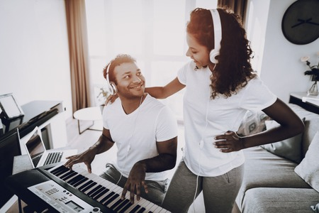 Afro American Couple Listening With Headphones Synthesizer Playing. Happy Songwriter. Morning Leisure. Digital Format Sound Record. Working Musician. Musical Hobby. Hands On Keyboard. Stock Photo
