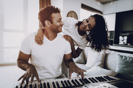 Girl Is Hanging A Boyfriend Playing Synthesizer. Happy Songwriter. Morning Leisure. Digital Format. Working Musician. Musical Hobby. Hands On Keyboard. Afro American Couple. Take A Rhytm. Stock Photo