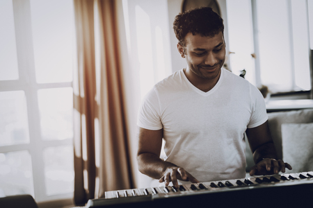Afro American Young Man Is Playing Synthesizer At Home. Happy Songwriter. Morning Leisure. Digital Format Sound Record. Working Musician. Musical Hobby. Hands On Keyboard. Cheerful Professional. Banco de Imagens