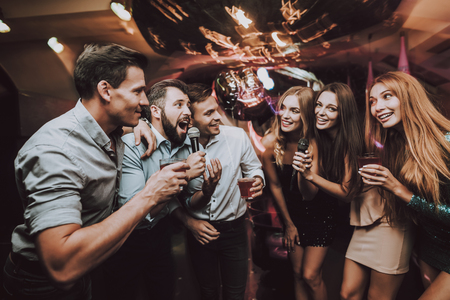 Smiling Girl. Vocal Battle. Cheerful. Singing Songs. Beautiful Girls. Friends at Karaoke Club. Karaoke Club. Celebration. Young People. Party Maker. Girls Sing. Smile. Trendy Nightclub. Have Fun. Standard-Bild