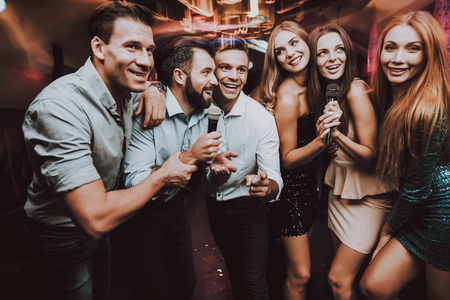 Cheerful. Smile. Smiling Girl. Singing Songs. Beautiful Girls. Friends at Karaoke Club. Karaoke Club. Celebration. Young People. Party Maker. Girls Sing. Trendy Nightclub. Have Fun. Stock Photo