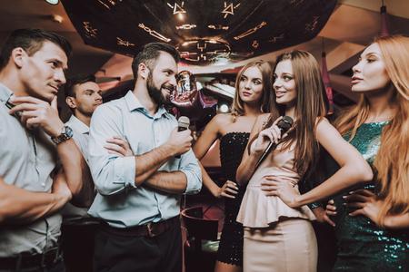 Battle. Cheerful. Singing Songs. Have Fun. Beautiful Girls. Friends at Karaoke Club. Karaoke Club. Celebration. Young People. Party Maker. Girls Sing. Smile. Trendy Nightclub. Smiling Girl.