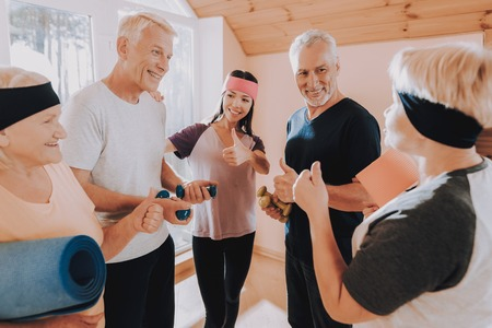 Thumbs Up. Active Retiree. Instructor. Men do Exercises. Equipment. Therapeutic Gymnastics. Have Fun. Wearing Sport Uniform. Healthcare Lifestyle. Group Elderly Women. Nursing Home. Smiling Patient.