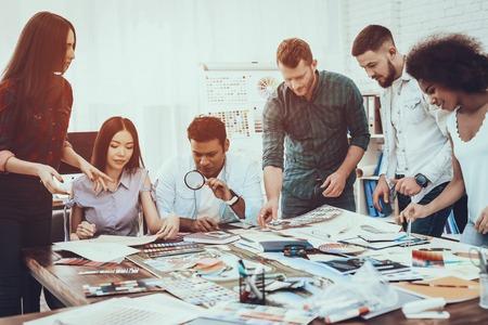 Idee generieren. Farben für Design. Verschiedene Rassen. Projekt. Landschaft. Designer. Gruppe. Zusammenarbeit. Designer. Zusammenarbeit. Brainstorming. Arbeit. Tabelle. Großes helles Büro. Diskutieren. Proben. Schemata.