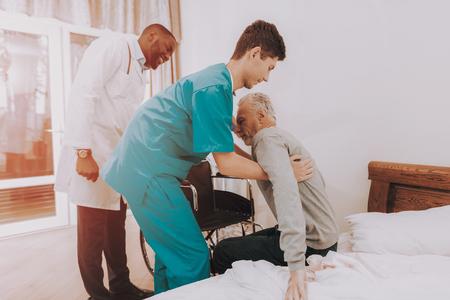 Sors du lit. Infirmière aide. Homme âgé. Asseyez-vous en fauteuil roulant. C'est difficile à faire. L'homme se sent faible. Docteur en clinique. Le docteur aide à se lever. Patient. Patient en fauteuil roulant. Maison de repos. Réhabilitation.