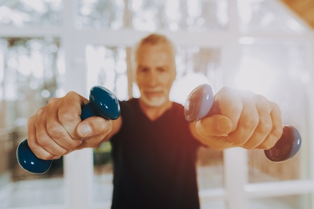 Elderly Hold Dumbbells. Therapeutic Gymnastics. Nursing home. Looks Confident in Abilities. Man. Active Retiree. Have Fun. Wearing Sport Uniform. Healthcare Lifestyle. Exercises. Smiling Patient. Stok Fotoğraf