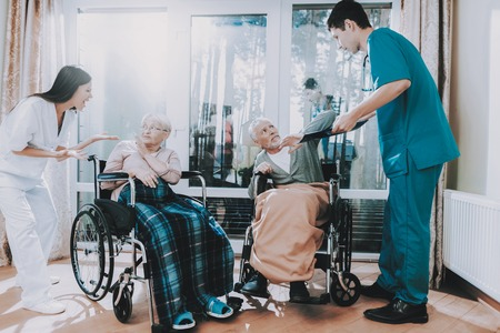 Medical Workers. Argue with Elderly Couple. Nursing Home. Very Emotional. Elderly Very Frightened. Sitting in Wheelchair. Awful. Current Affairs. Cause Trouble. Caus an Accident. Bad Service. Stock Photo
