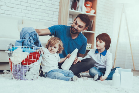 Leisure Time. Man. Smile. Two Boys. Help Wash Clothes. Father. Baby with Bright Hair. Smiling Kids. Spends Time. Happy Together.Home Time. Family. Holidays. Father Two Boys. Dirty Laundry. Basket. Stock Photo