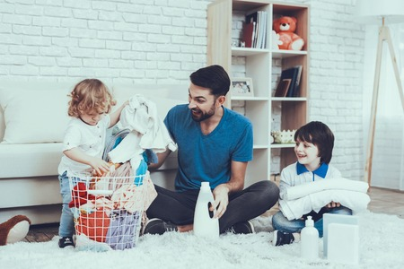 Dirty Laundry. Two Boys. Help Wash Clothes. Father. Baby with Bright Hair. Smiling Kids. Spends Time. Happy Together. Leisure Time. Man. Smile. Home Time. Family. Holidays. Father Two Boys. Basket.