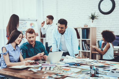 Work. Table. Landscape. Designers. Group. Generate Idea. Teamwork. Designers. Different Races. Project. Cooperation. Brainstorming. Large Bright Office. Discuss. Colors for Design. Samples. Schemes. Stock Photo