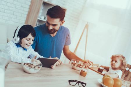 Tablet. Father. Leisure Time. Smiling Kids. Sweet Baby. Enjoy. Jam. Childhood. Boy. Baby with Bright Hair. Child on Chair. Smile. Spends Time. Happy Together. Having Breakfast. Man. Home Time. Stock Photo