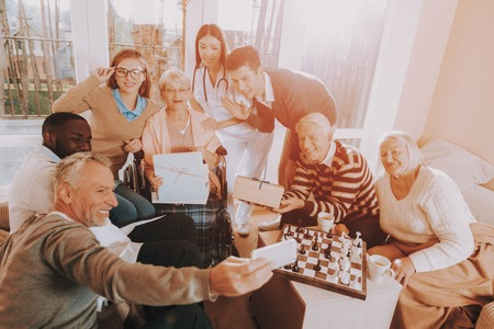 Family Selfie. Mobile Phone. Birthday Party. Celebration. Gifts. Balloons. Guests. Young and Old People. Nursing Home. Congratulate. Elderly Woman. Happy. Wheelchair. Madly Happy Retiree. Surprised. Stockfoto