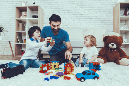 Spends Time. Happy Together. Leisure Time. Smiling Kids. Father. Father Two Boys. Man. Smile. Home Time. Baby with Bright Hair. Two Boys. Plays Games. Toys. Teddy Bear. Cars. Holidays.